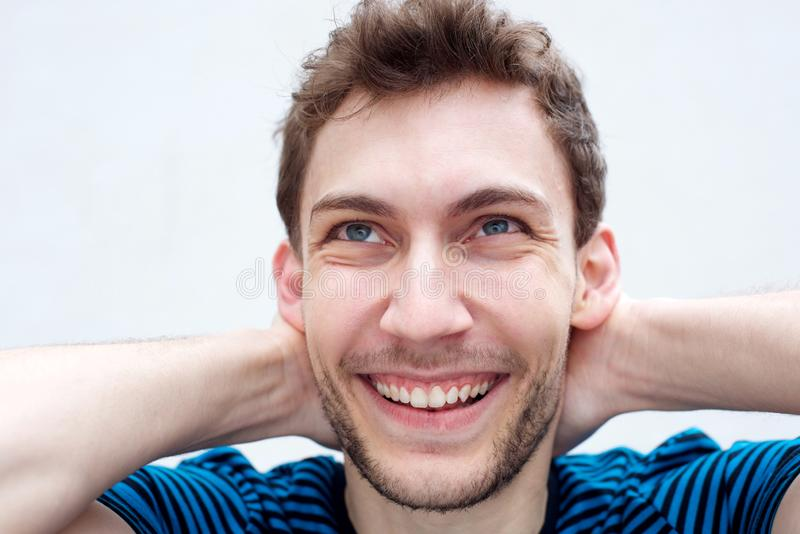 Close up young man smiling with hands behind head by white background royalty free stock images
