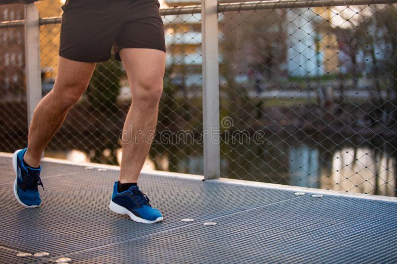 Sporty man legs. Close up of young man sporty legs running outdoor along a bridge in the morning. Self overcome conquering obstacles and win. Healthy lifestyle royalty free stock images