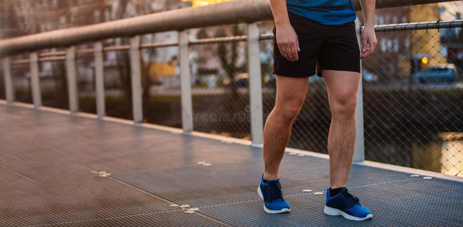 Panoramic banner of young man sporty legs running outdoor. Close up of young man sporty legs running outdoor along a bridge in the morning. Self overcome stock image