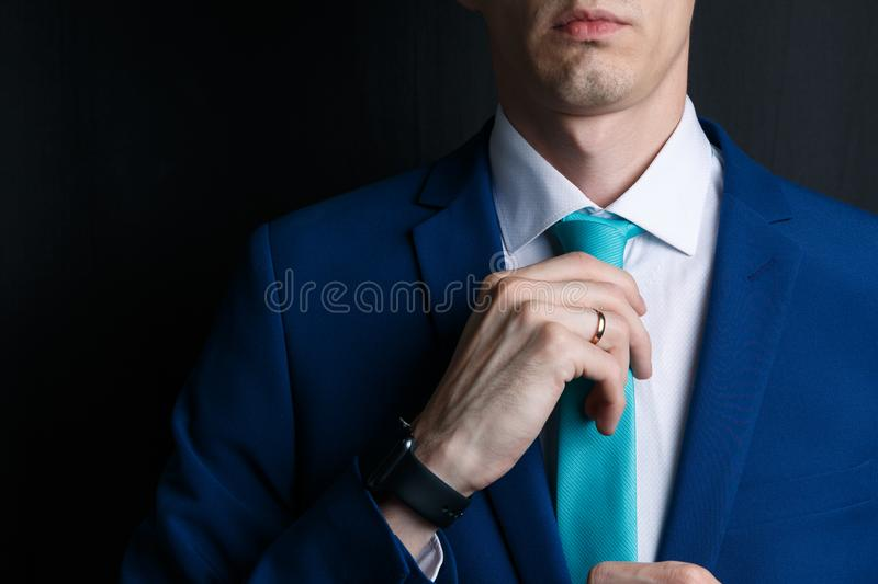 Close-up young man in an suit. He is in a white shirt with a tie. The man straightens his tie royalty free stock images