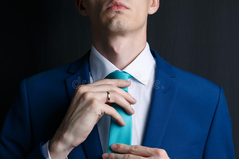 Close-up young man in an suit. He is in a white shirt with a tie. The man straightens his tie, his face unshaven royalty free stock photos