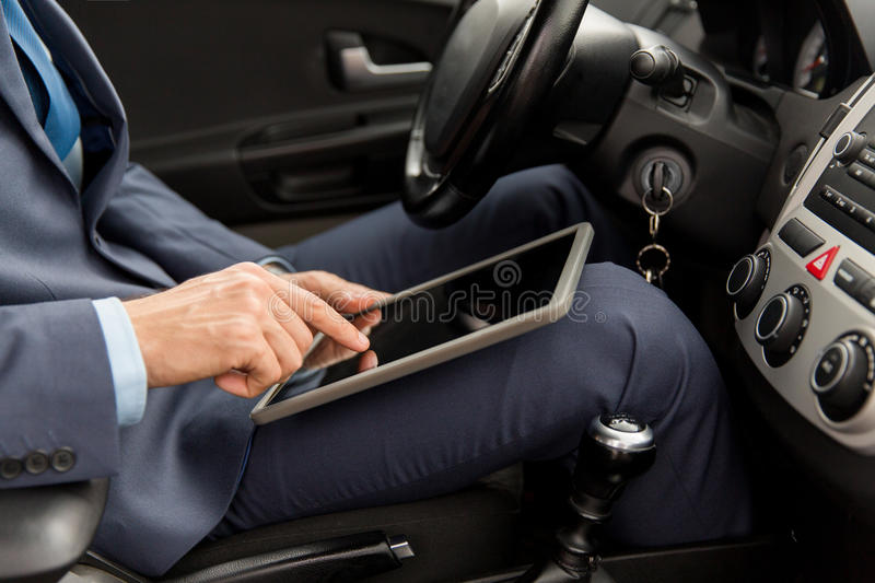 Close up of young man with tablet pc driving car. Transport, business trip, technology and people concept -close up of young man with tablet pc computer driving royalty free stock image