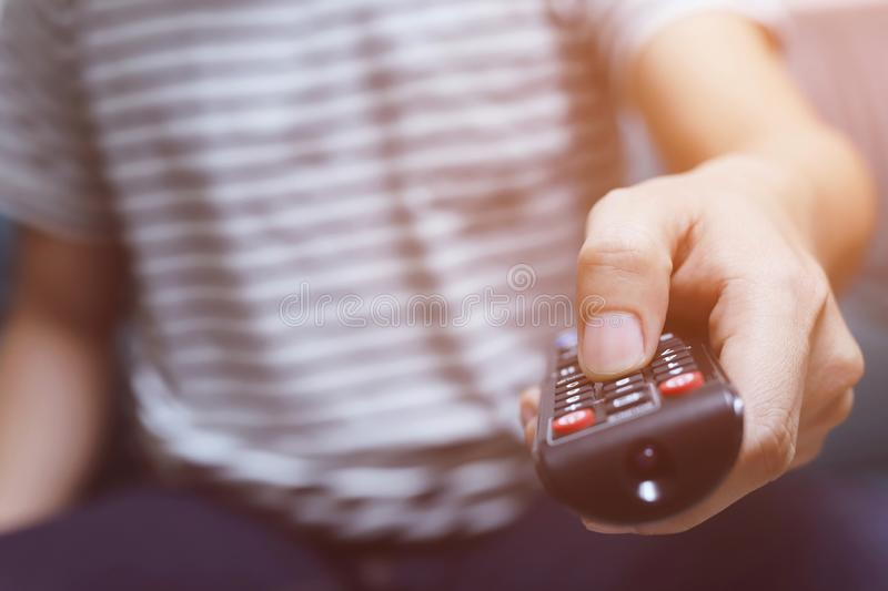 Close up young man using television remote control stock image