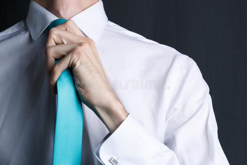 Close-up young man in a white shirt with a tie. The man straightens his tie, his face unshaven. Businessman in a white shirt stock image