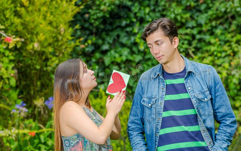 Close up of young man with a disgusting face looking at the girl and beautiful woman begging to his crush with a letter. Close up of young men with a disgusting stock photography