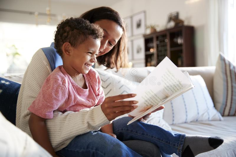 Close up of young mother sitting on a sofa in the living room reading a book with her toddler son, who is sitting on her knee, sid stock photo