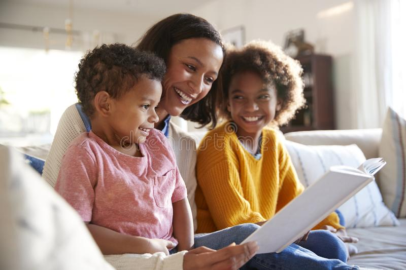 Close up of young mother sitting on a sofa in the living room reading a book to her two children, close up, side view royalty free stock photography