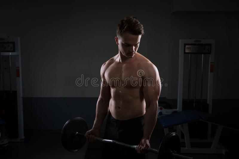Close up of young muscular man lifting weights over dark background royalty free stock photos