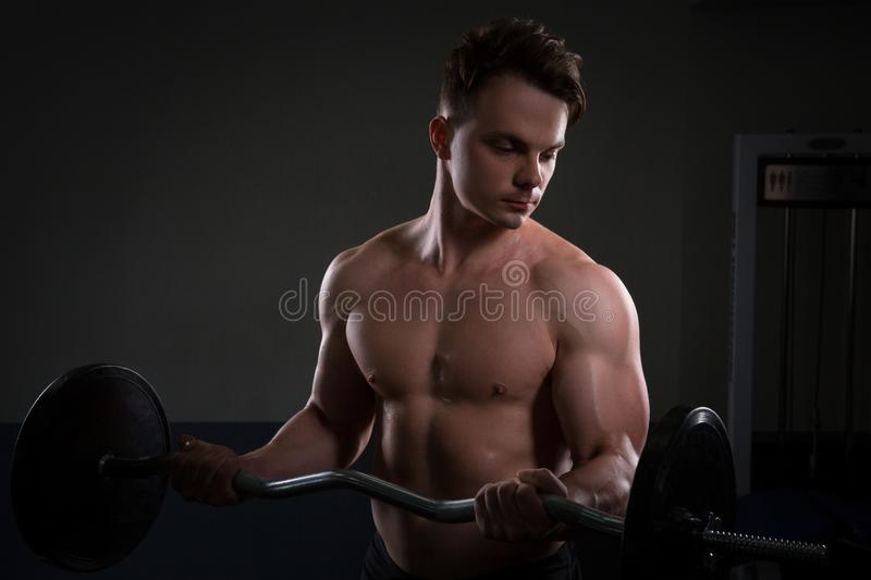 Close up of young muscular man lifting weights over dark background royalty free stock photography