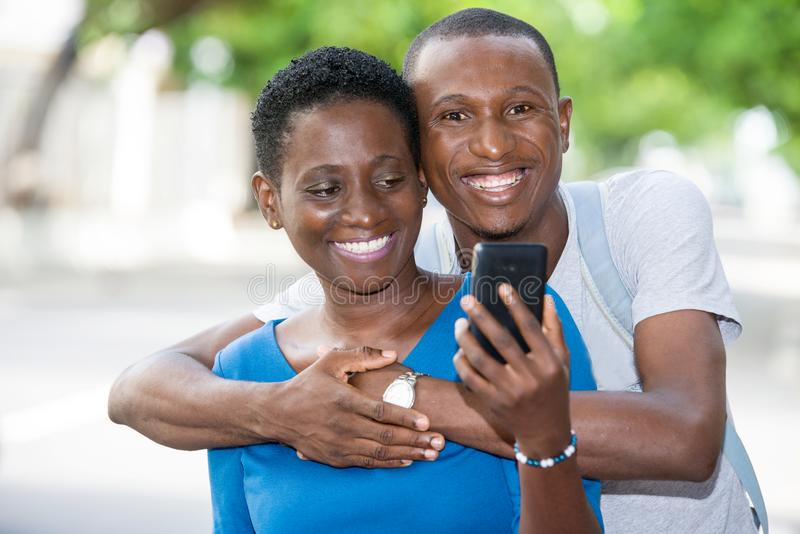 Close up of young people, happy. Young people standing with mobile phone, embracing smiling royalty free stock photos