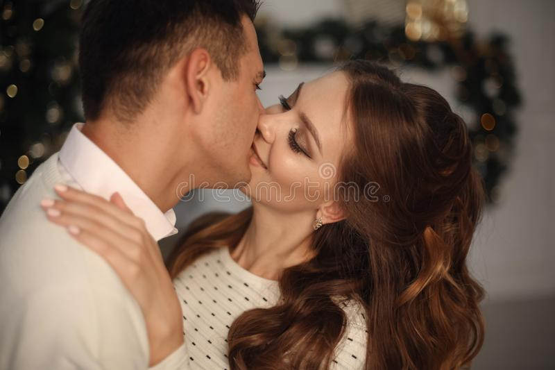 Close-up of young romantic couple is kissing at home. Happy smiling woman emrace her handsome man. royalty free stock photos