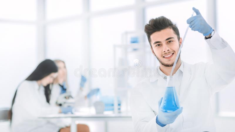 Close up. the young scientist makes the analysis of the liquid in the flask. Photo with copy space stock photo
