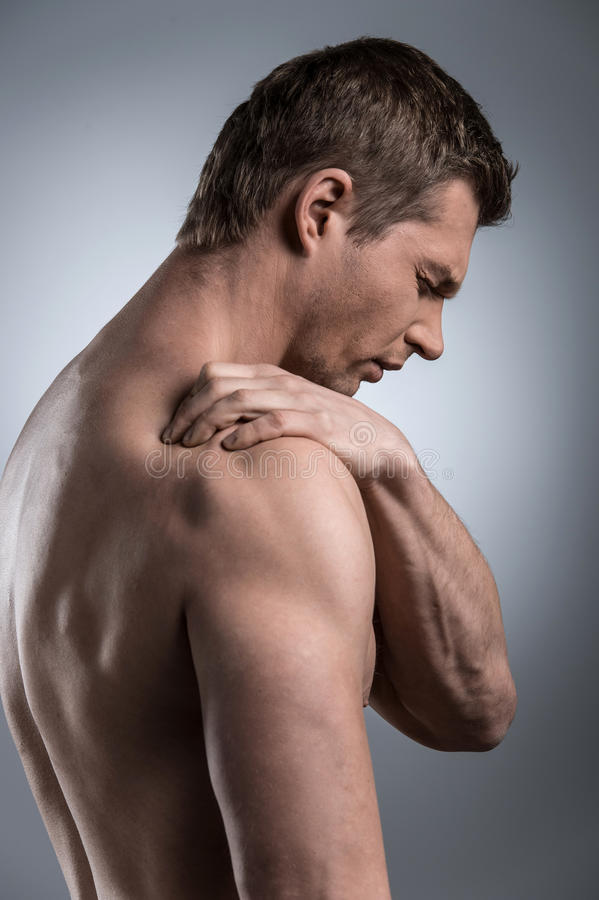 Close-up of young shirtless man with shoulder pain. stock photo