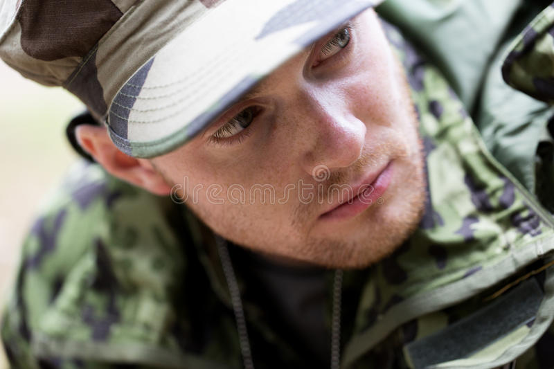 Close up of young soldier in military uniform. War, army and people concept - close up of young soldier in military uniform royalty free stock image
