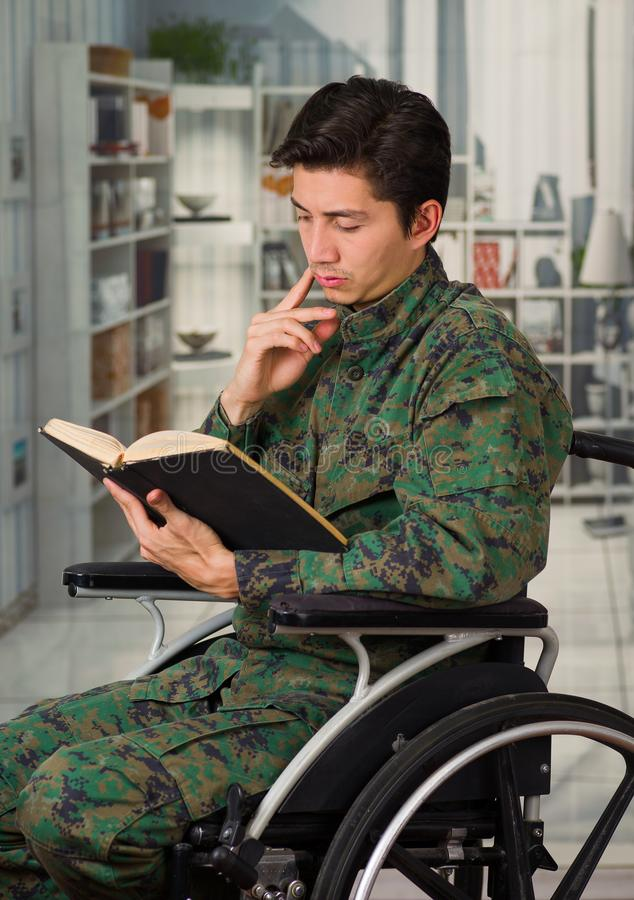 Close up of a young soldier sitting on wheel chair reading a book at home, in a blurred background.  stock photography