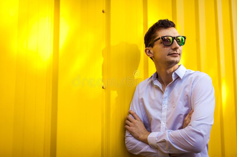 Close up of young stylish man in white shirt standing against yellow wall outdoors. Summer fashionable outfit. stock photo
