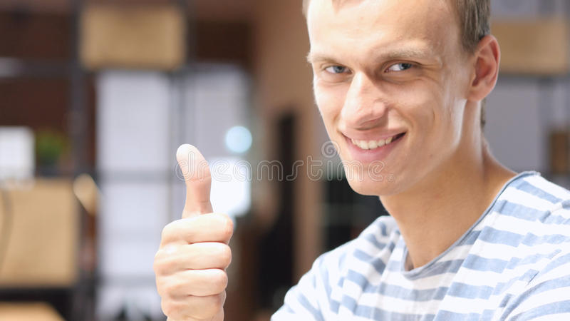Close up of Young Successful Man, Showing Thumbs Up in Office stock photo