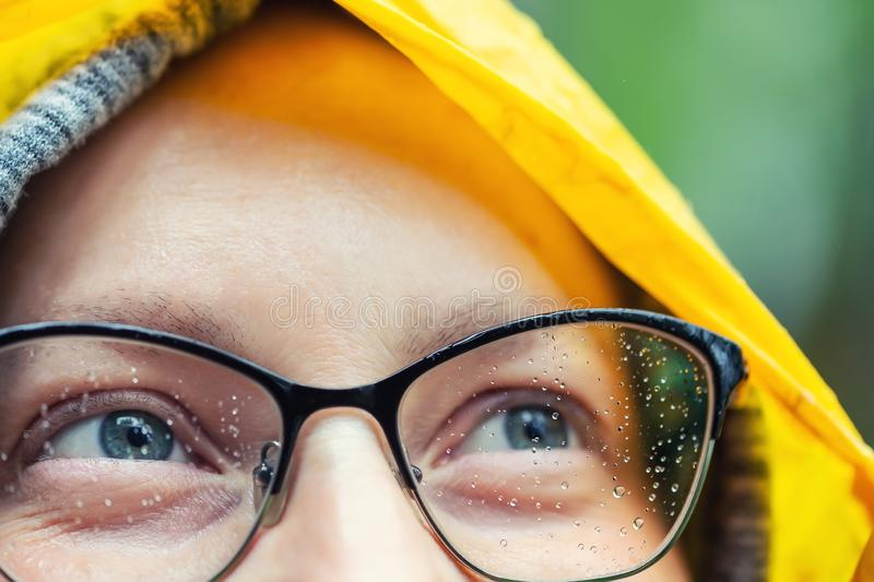 Close-up young tired happy woman portrait wearing glasses with raindrops and bright yellow raincoat hood during rain outdoors stock image