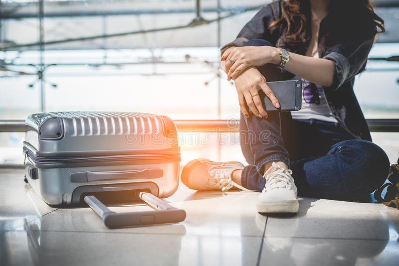 Close up of young woman with bag and suitcase luggage waiting for departure while sitting in airport lounge. Female traveler and. Tourist theme. High season and royalty free stock photos