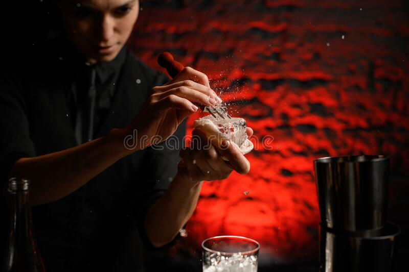 Close-up young woman bartender in black clothes breaks ice with special device. Brick wall illuminated in red at background stock image