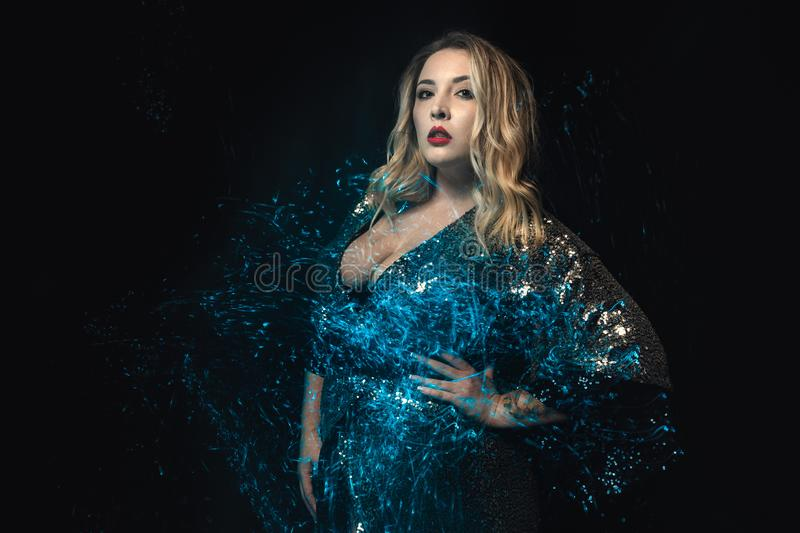 Close-up young woman blonde in shiny blue dress. Mixed lights effect. Half length photo. Stylish blonde in glamour dress looking at the camera. Black stock image