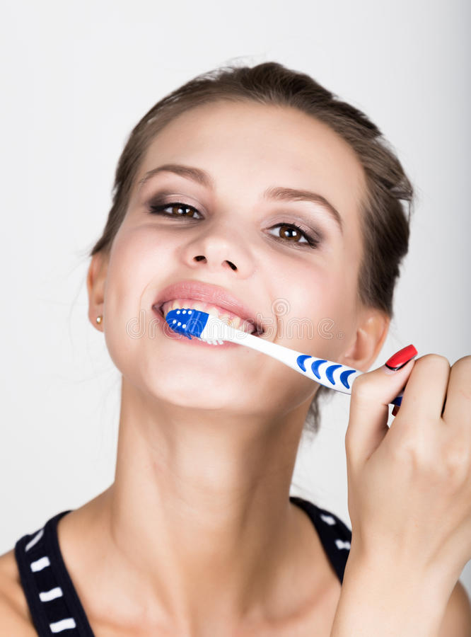 Close-up of a young woman is brushing her teeth. Dental health care concept. royalty free stock photos
