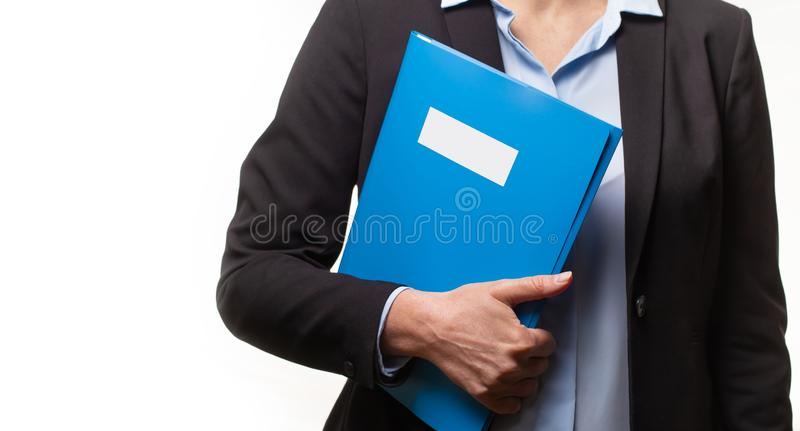 Close up of a young woman in a business suit holding a file. royalty free stock images