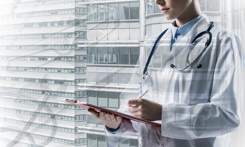 Modern medical industry concept. Close up of young woman doctor in white medical suit writing in notebook while standing against city view and medical stuff on royalty free illustration