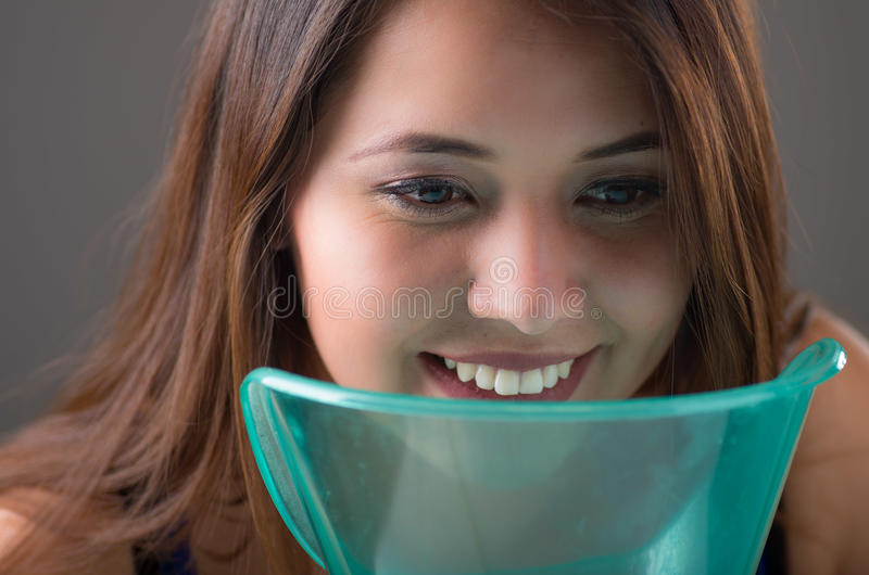 Close up of a young woman doing inhalation with a vaporizer nebulizer machine on grey background stock photography