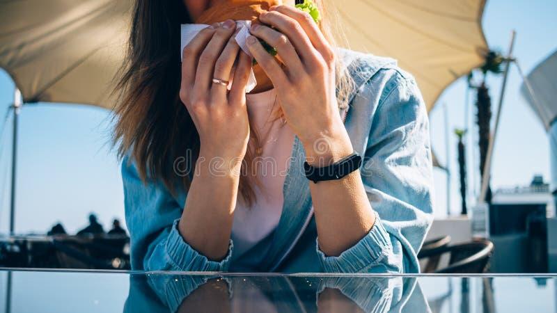 Close-up of young woman eating hamburger royalty free stock photo