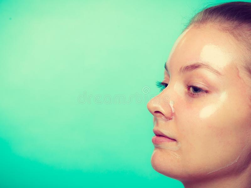Close up woman in facial peel off mask. Close up young woman in facial peel off mask. Peeling. Beauty and skin care. Side view royalty free stock photos