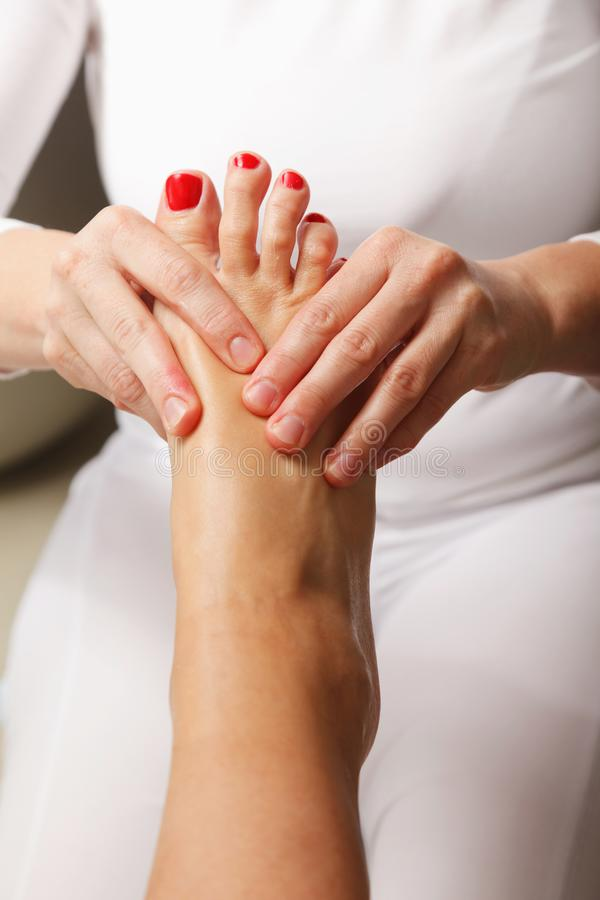 Close-up of young woman is getting foot massage stock images