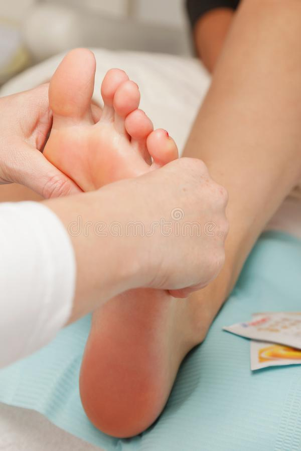 Close-up of young woman is getting foot massage stock photos