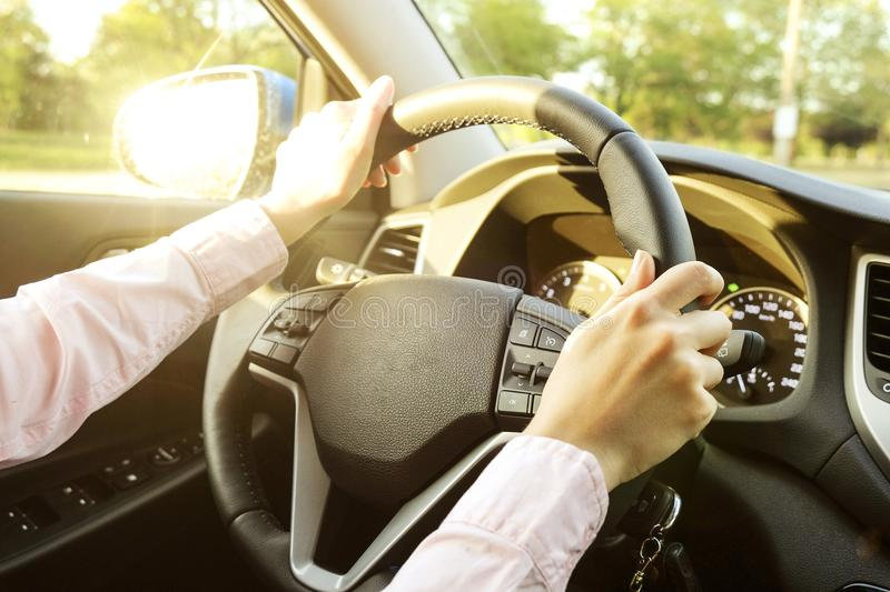 Car interior with female driver sitting behind the wheel, soft sunset light. Luxurious vehicle dashboard and electronics. stock images