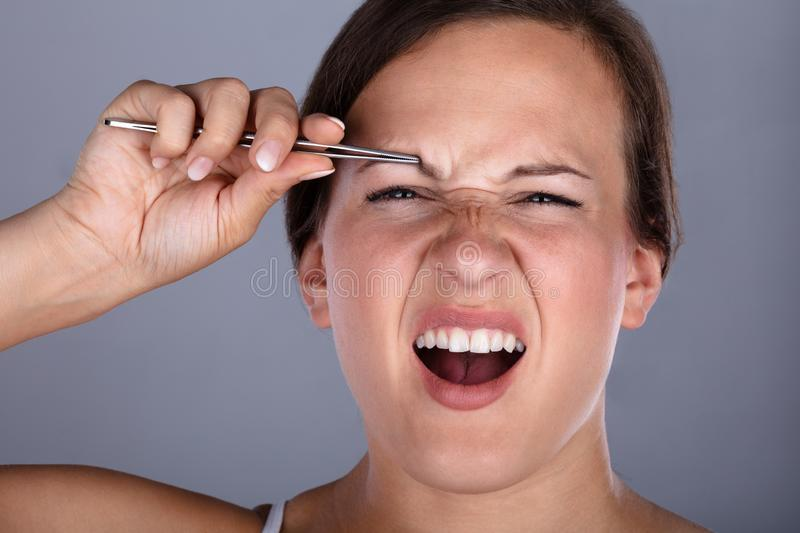 Woman Having Pain While Plucking Eyebrow Hair With Tweezers royalty free stock images