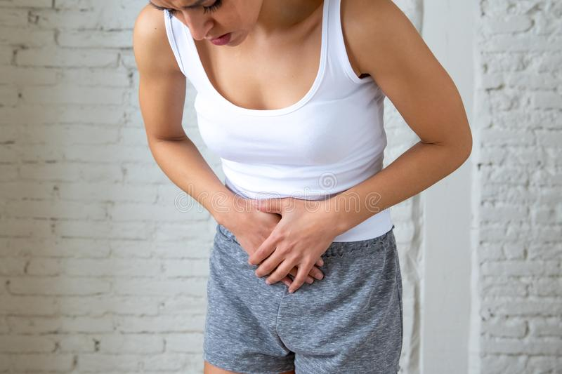 Close up of beautiful woman body suffering from stomachache, period pain and menstrual cramps. Close up of a young woman having painful stomachache holding hands royalty free stock photography