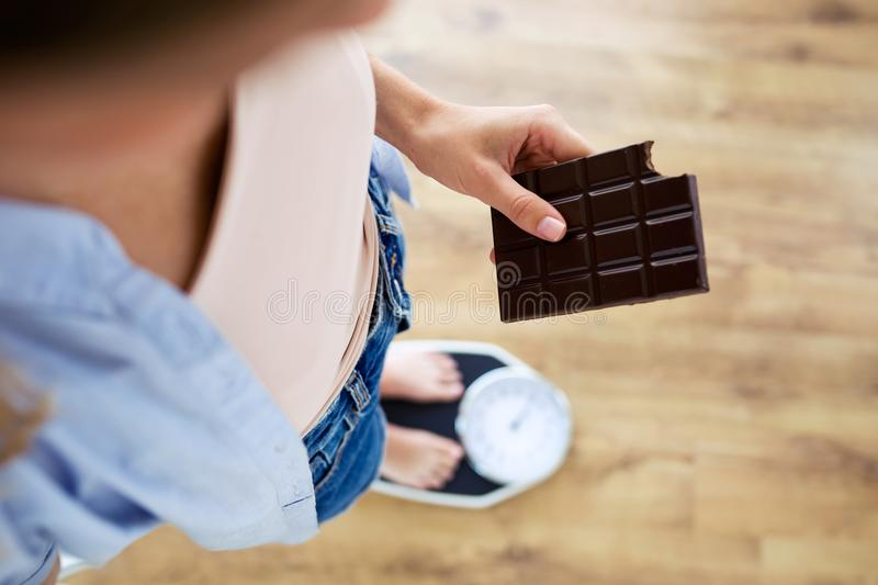 Young woman holding chocolate bar on a weigh scale at home. stock photo