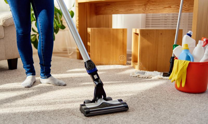 Close up of young woman in jeans cleaning carpet with vacuum cleaner in living room, copy space. Housework, household. royalty free stock photography