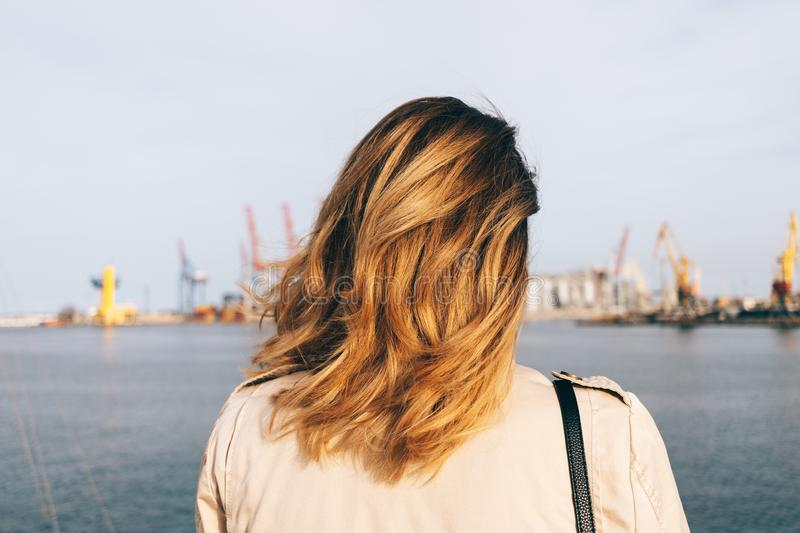 Close-up young woman looking at sea port standing on embankment royalty free stock photo