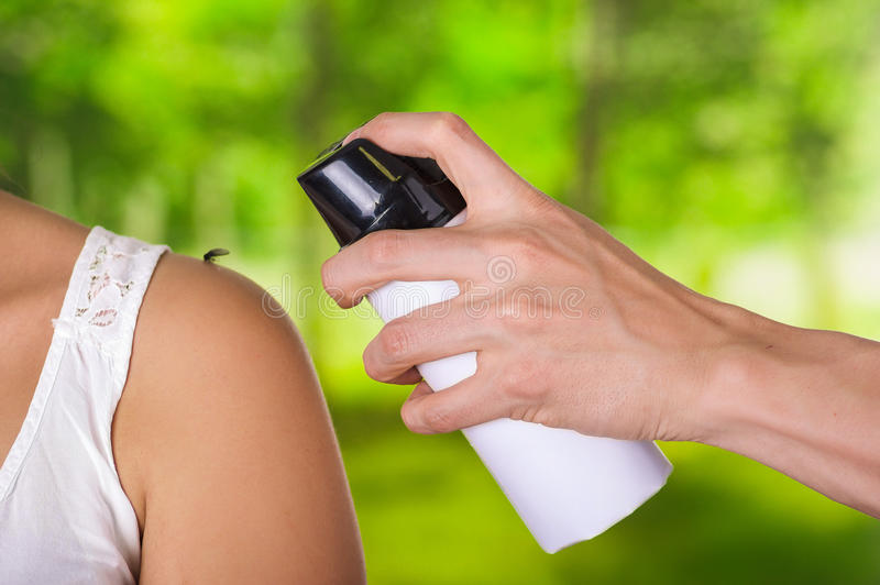 Close up of young woman with a mosquito in her shoulder while a man hand is using a spay over the insect to kill it, in. A blurred background royalty free stock photography