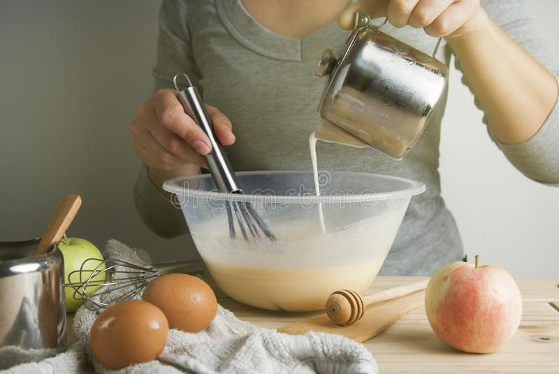 Close-up young woman`s hands holding whisk and bowl while making pie, cake. Female cooking dough for pie on wooden table. Preparring dessert. Isolated stock images