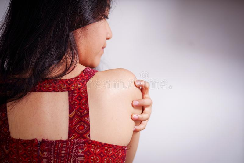 Close up of a young woman scratching her shoulder with her hand after being raped and suffering sexual abuse, in a white royalty free stock images