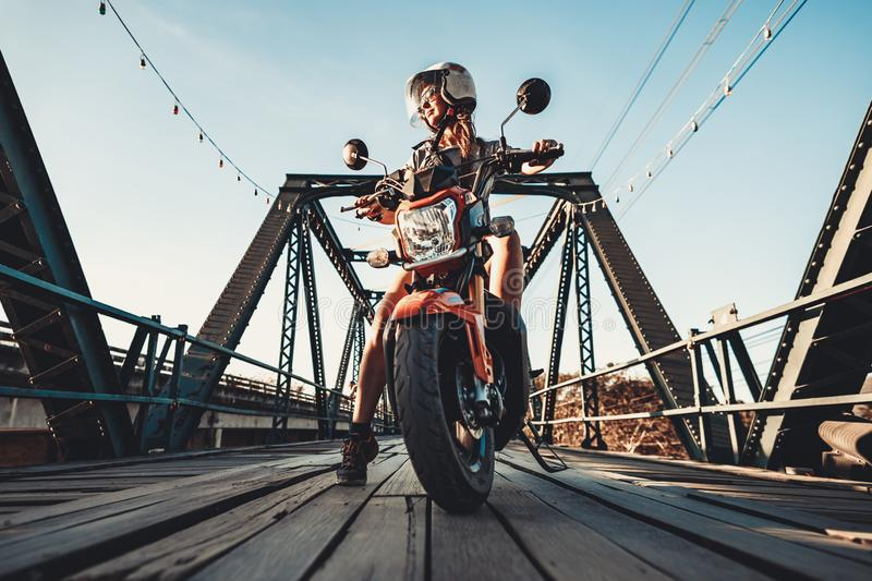 Close-up young woman sitting on the motorbike. Stop over on the new repaired vintage wooden bridge. Biker background. Outdoor extreme activity. Wild road royalty free stock photo