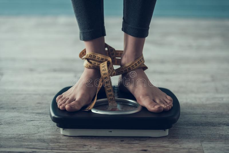 Close up. Young Woman Standing on Weigher on Floor royalty free stock image