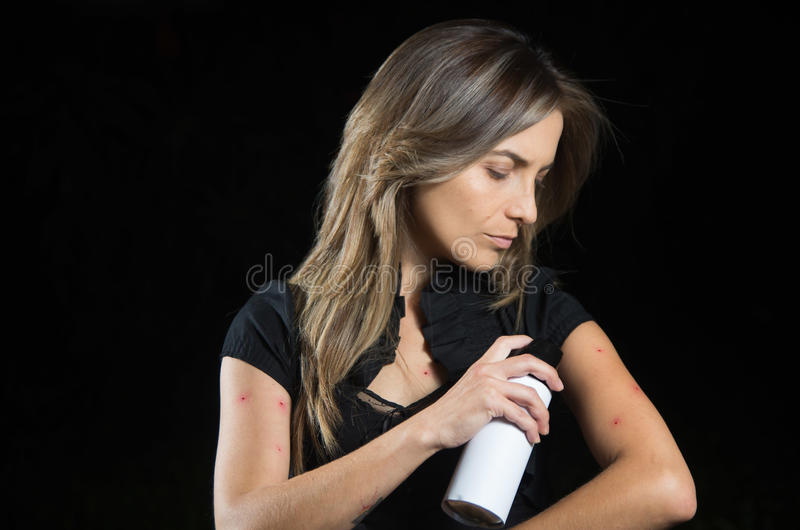 Close up of young woman suffering from itch after mosquito bites, using a spay over the insect bite, allergic skin. Close up of young woman suffering from itch stock photo