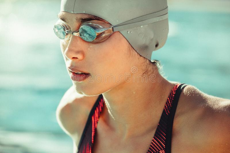Focused professional swimmer. Close up of young woman swimmer in swim cap and goggles. Focused professional swimmer looking away stock image