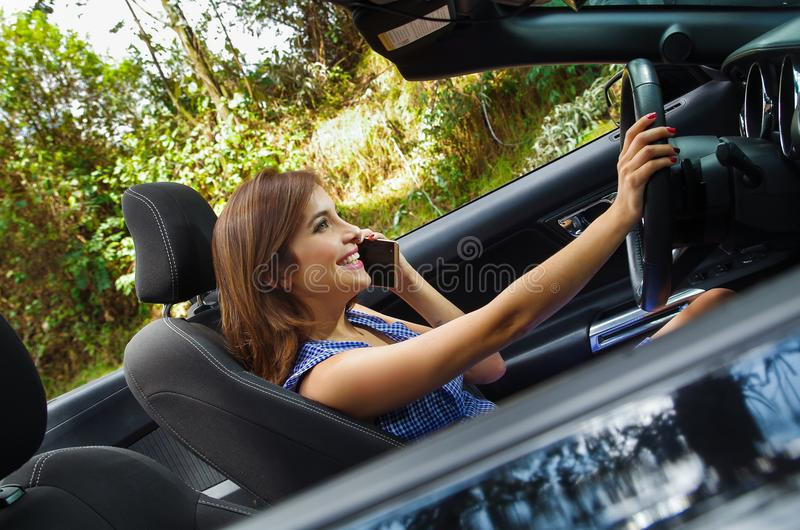 Close up of young woman using her cellphone inside of the black car, while driving her car with one hand, in a blurred stock photo