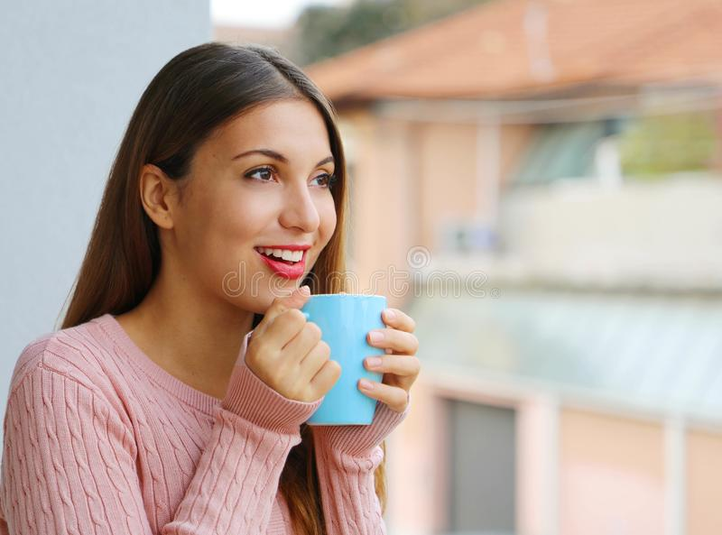 Close up of young woman with warm sweater holding mug with hot drink at home on balcony outdoors royalty free stock image