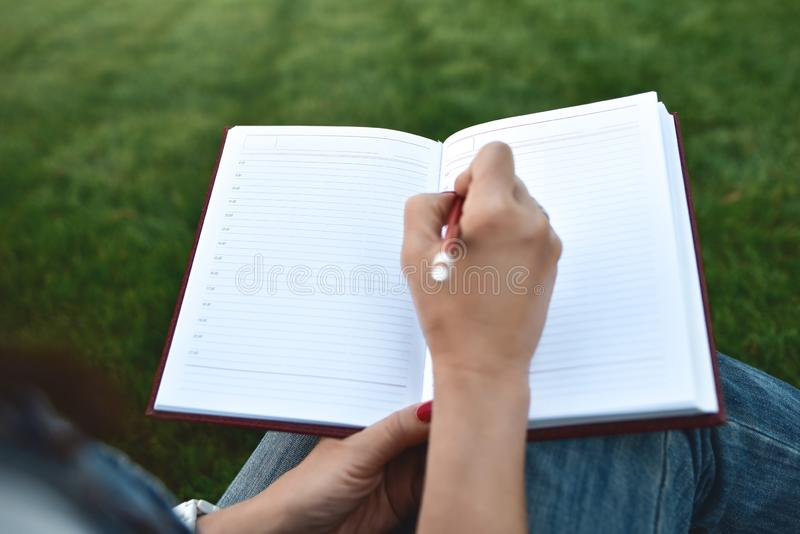 Close up young women writing on notebook in park, concept in education and knowledge. Close up young women writing on notebook in park. education and knowledge royalty free illustration