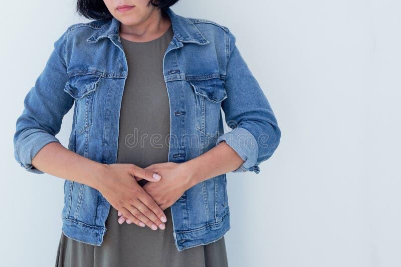 Close-up zieke jonge vrouw op bank concept die aan buikpijn lijden stock foto